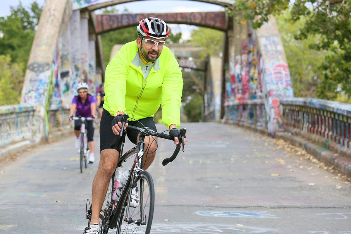 Man cycling over bridge